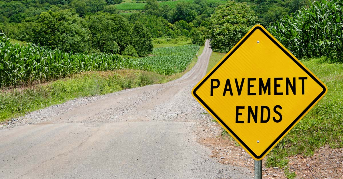 "road with ""pavement ends"" sign"